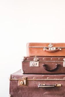 Três malas velhas do vintage contra um fundo claro da parede. estilo retrô rústico