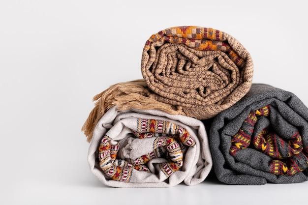 Três mantas quentes enroladas acessórios para clima frio de material natural copiar espaço