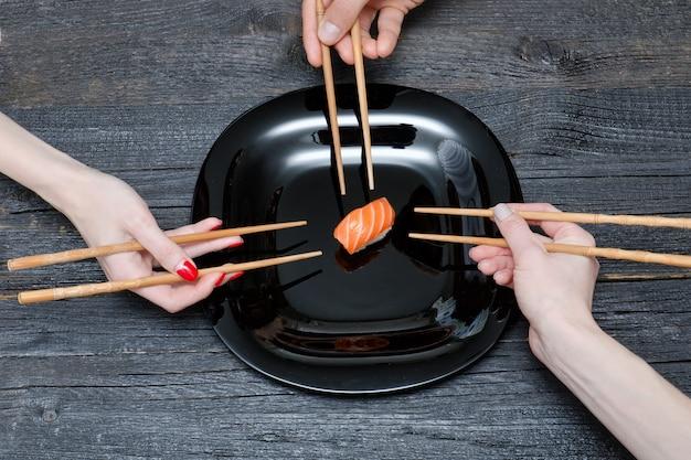 Três mãos com pauzinhos e sushi.