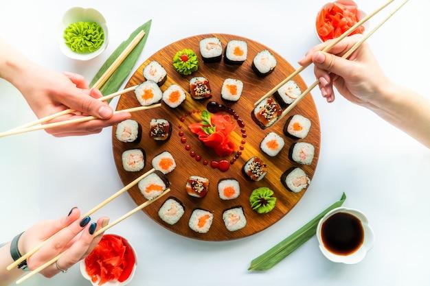 Três mãos segurando um sushi diferente acima da superfície redonda de madeira com gengibre, molho de soja e wasabi