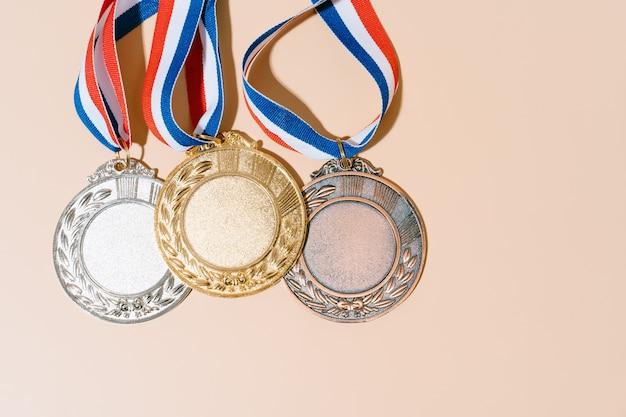 Três medalhas (ouro, prata, bronze) em fundo pastel. conceito de prêmio e vitória. copiar espaço