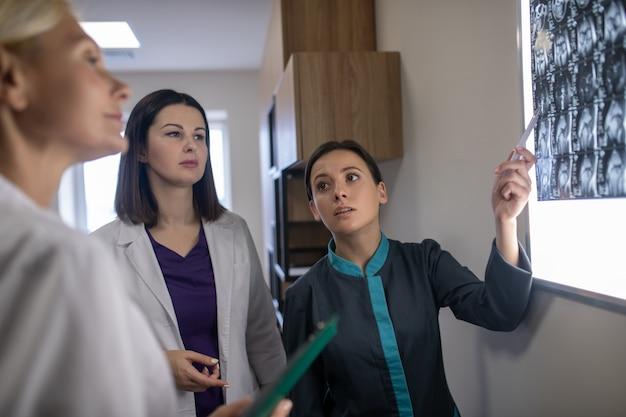 Três médicas discutindo seriamente sobre ressonância magnética de cérebro
