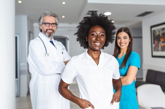 Três médicos e enfermeiras parados no corredor de um hospital, vestindo jalecos e jalecos.