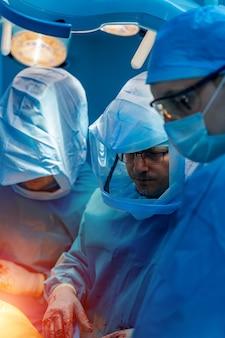 Três médicos em equipamentos de proteção individual. fato branco para proteger a infecção covid 19. operação de cirurgia e neurocirurgia.