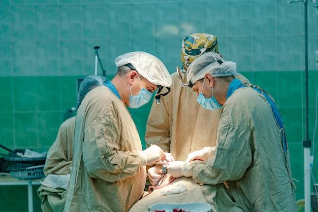 Três médicos realizam uma operação do paciente com a participação de uma enfermeira na sala de cirurgia