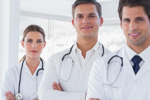 Três médicos sorridentes com casacos de laboratório