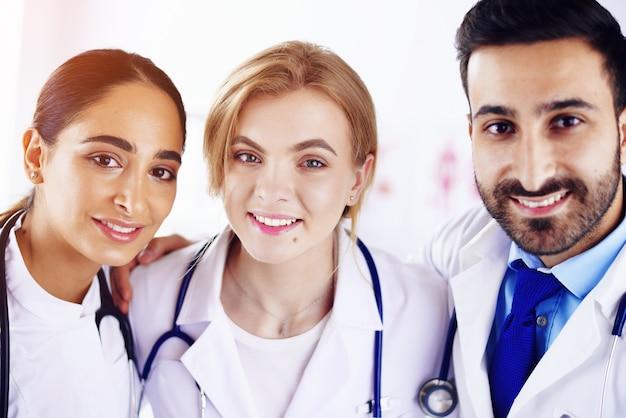 Três médicos sorridentes todos juntos em um hospital. médicos multirraciais