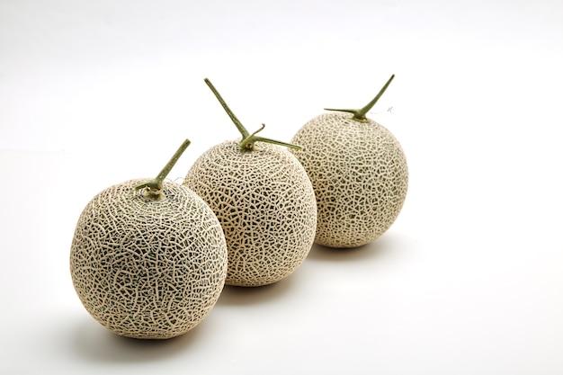Três melão cantaloupe em branco