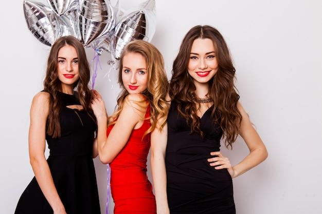 Três melhores amigas celebram o aniversário em ambientes fechados, usando elegantes vestidos de noite e maquiagem brilhante. meninas, abraçando e mostrando sinais com as mãos.