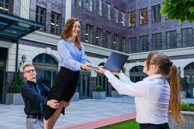Três membros da acroyoga - base, flyer e observador fazem composição com laptop de doação, usam roupas de escritório em meio urbano