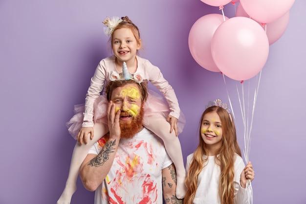 Três membros da família posam dentro de uma parede roxa. duas filhas e pai engraçados se divertem, colorem rostos com aquarelas coloridas e comemoram o dia das crianças juntos conceito de entretenimento.