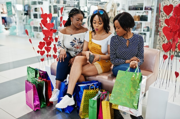 Três meninas afro-americanas bem vestidas bonitas com os sacos de compras coloridos que sentam-se no sofá na alameda e que olham o dinheiro da carteira.