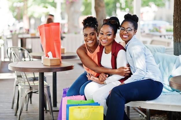 Três meninas afro-americanos ocasionais com sacos de compras coloridos que andam ao ar livre. mulher negra elegante às compras.