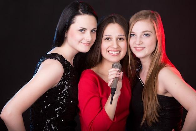 Três meninas bonitas com microfone