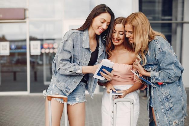 Três meninas bonitas em pé no aeroporto