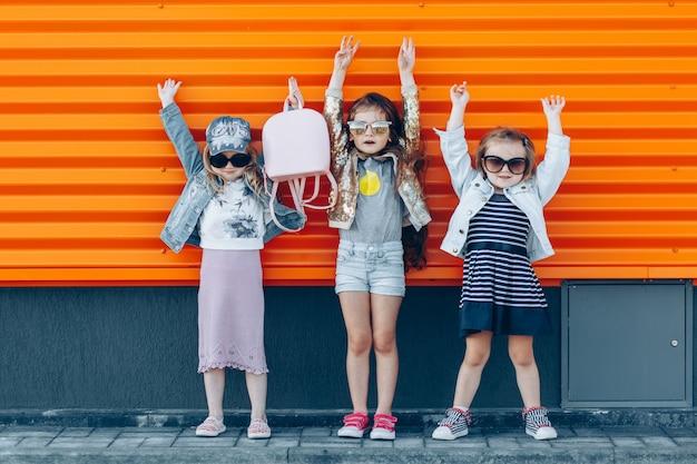 Três meninas bonitos à moda com as mãos levantadas