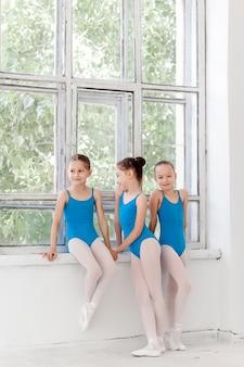 Três meninas de balé de pé e conversando juntos