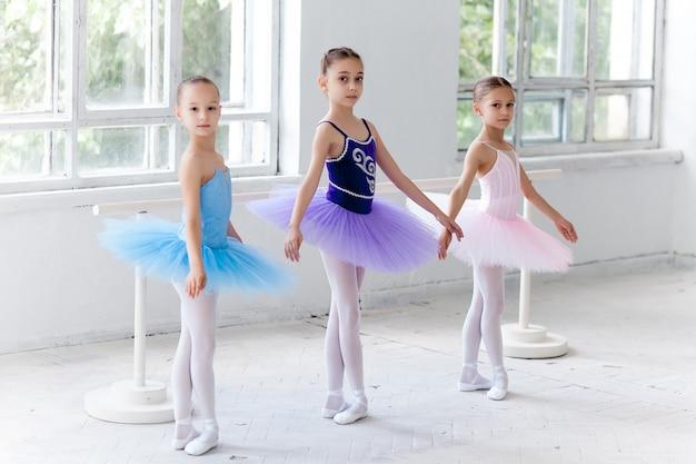 Três meninas de balé em tutu e posando juntos