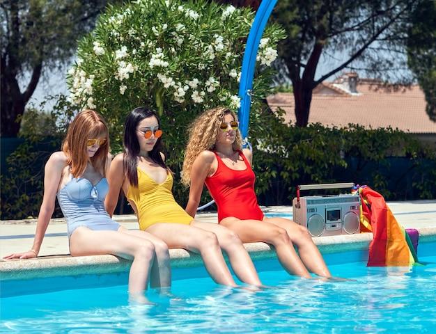 Três meninas de diferentes etnias relaxantes à beira da piscina