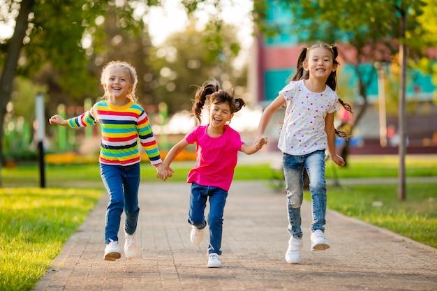 Três meninas de etnia asiática, europeia e indiana correm no parque no verão