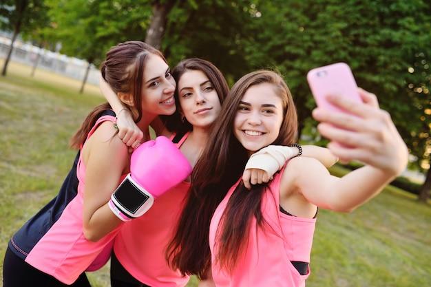 Três meninas de fitness tirar fotos de si mesmos em uma câmera de smartphone