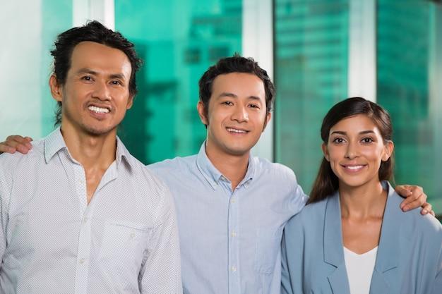 Três meninas de sorriso amigável do negócio pessoas abraçar
