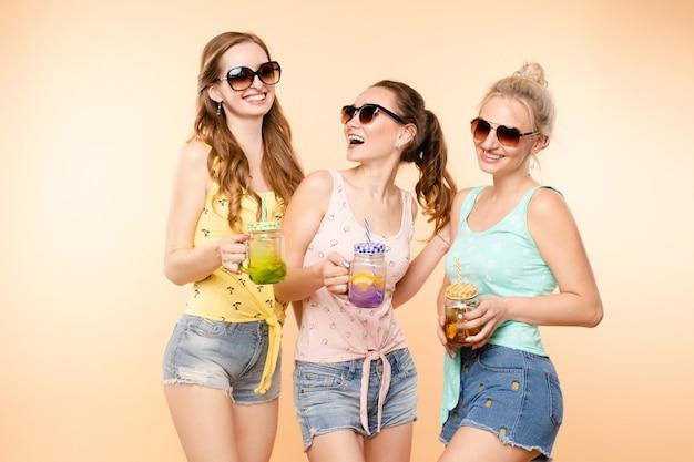 Três meninas desportivos bebendo suco fresco e posando
