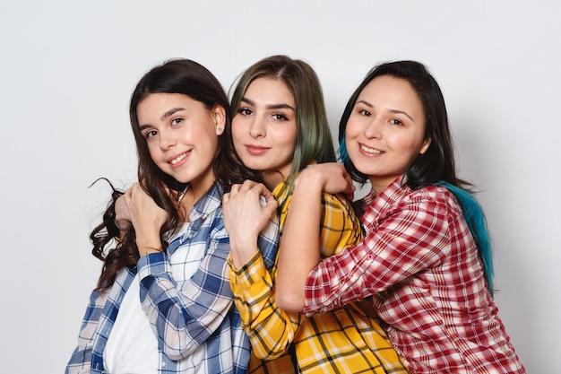 Três meninas elegantes melhores amigas. de pé juntos e se divertindo.