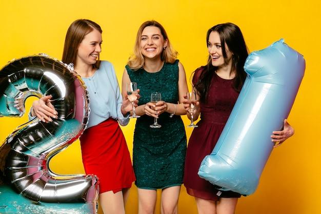 Três meninas elegantes usando vestidos, bebendo um champanhe, se divertindo