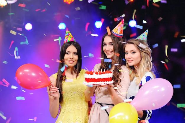 Três meninas em chapéus festivos e balões e bolo na mão.