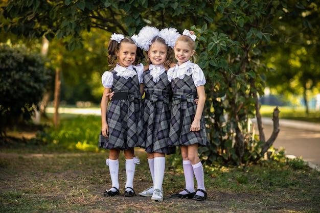 Três meninas em um uniforme escolar no pátio da escola