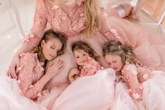 Três meninas em vestidos rosa dormem nos joelhos da mãe