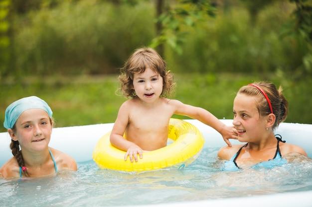 Três meninas estão nadando na piscina azul e brincando com bola