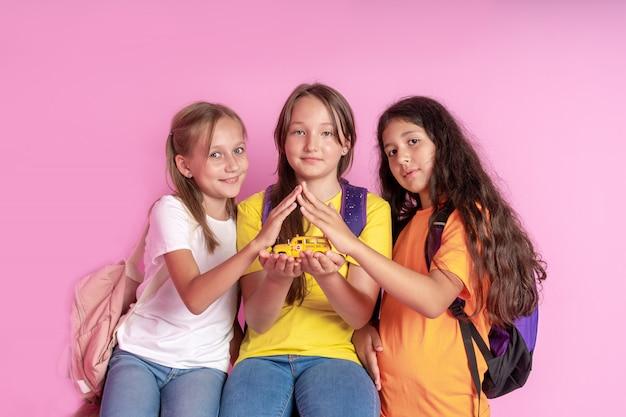 Três meninas estão segurando um ônibus escolar de brinquedo nas mãos