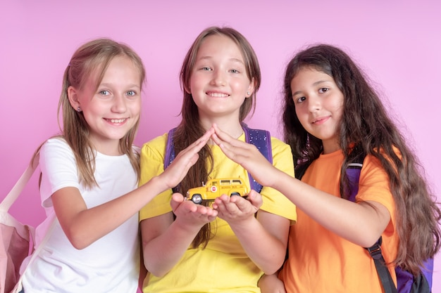 Três meninas estudantes estão segurando um ônibus escolar de brinquedo nas mãos.