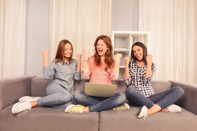 Três meninas felizes e bem sucedidas sentadas no sofá com um laptop