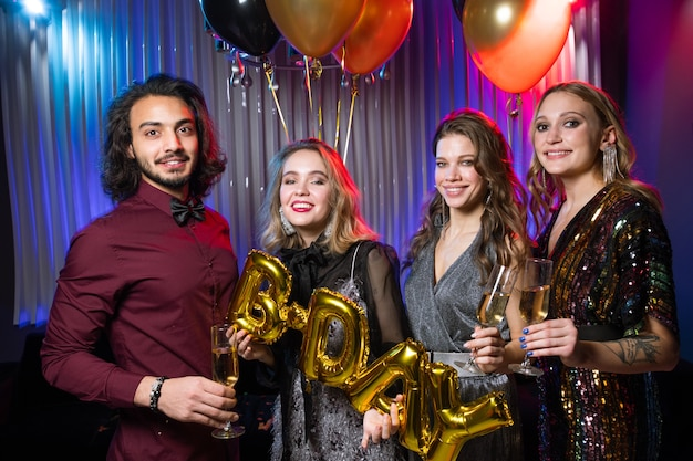 Três meninas felizes e um jovem segurando taças de champanhe e balões enquanto comemoram o aniversário na boate