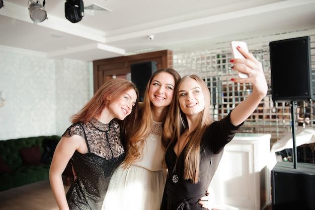 Três, meninas jovens, é, fazendo, selfie, foto, em, um, restaurante