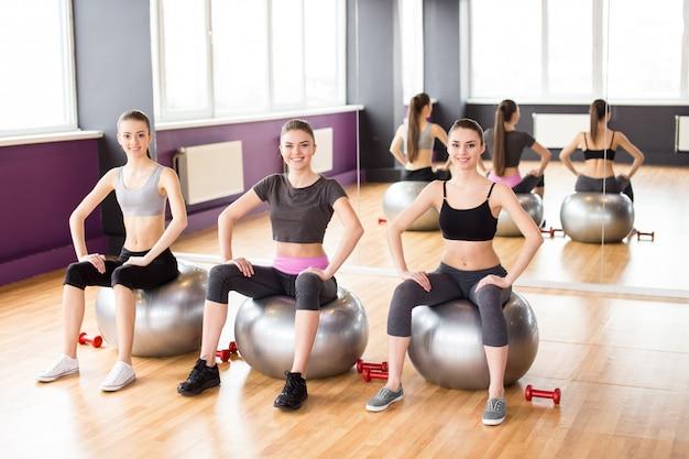 Três meninas sentam-se em bolas de fitness e exercício.