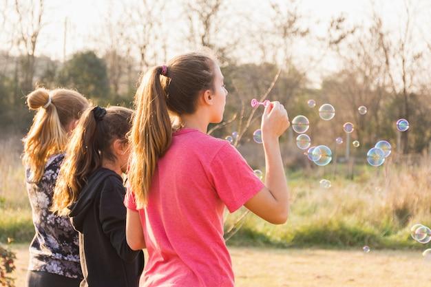 Três meninas, soprando, bolha, com, varinha, parque
