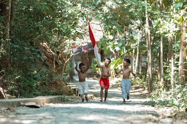 Três meninos correndo sem roupa segurando a bandeira vermelha e branca e levantando