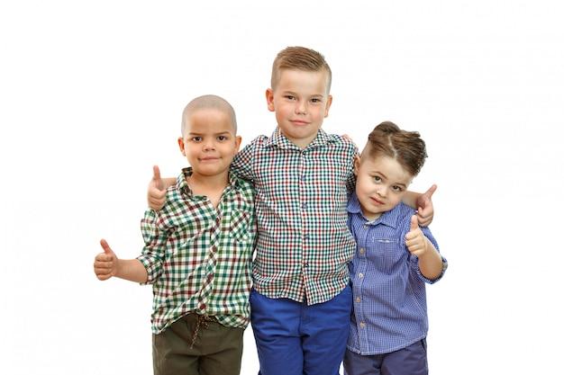 Três meninos estão juntos e levantam os polegares