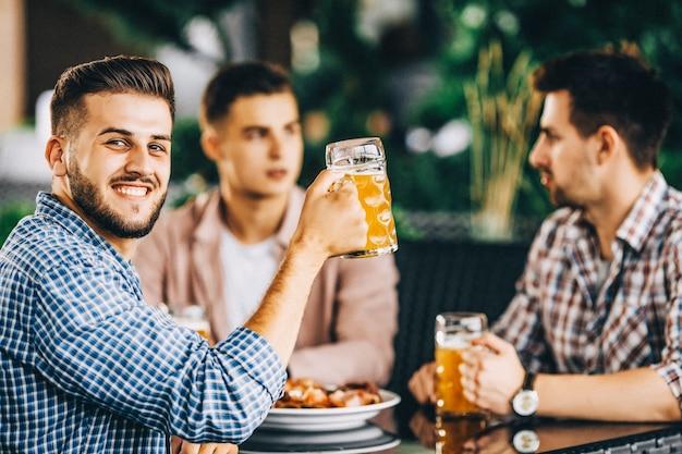 Três meninos se encontrando no bar, estão comendo e bebendo cerveja