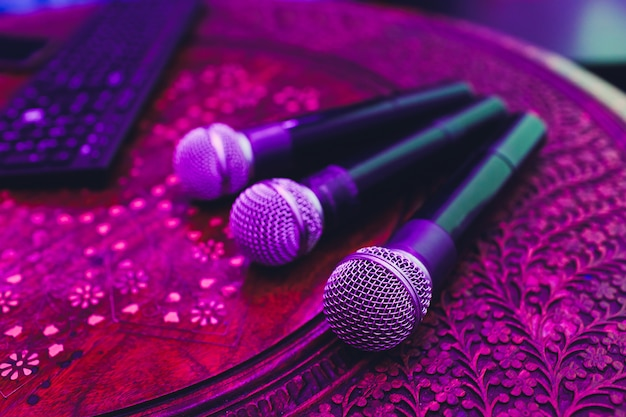 Três microfones em grupo na tabela vermelha com espaço de cópia.
