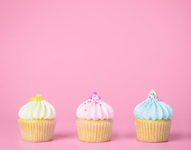 Três mini cupcakes pastel no espaço cópia rosa