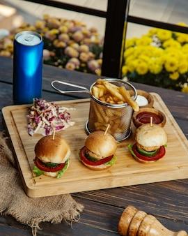 Três mini hambúrgueres de frango servidos com maionese e ketchup de batatas fritas
