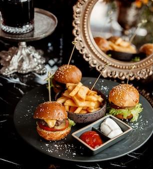 Três mini hambúrgueres servidos com batata frita, tomate e maionese