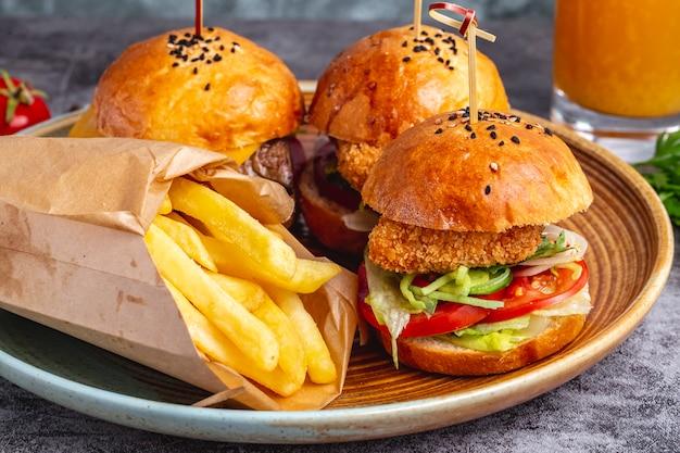 Três mini hambúrgueres servidos com batatas fritas em caixa de papel