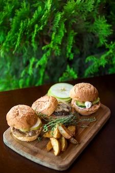Três mini hambúrgueres servidos com batatas fritas na tábua de madeira