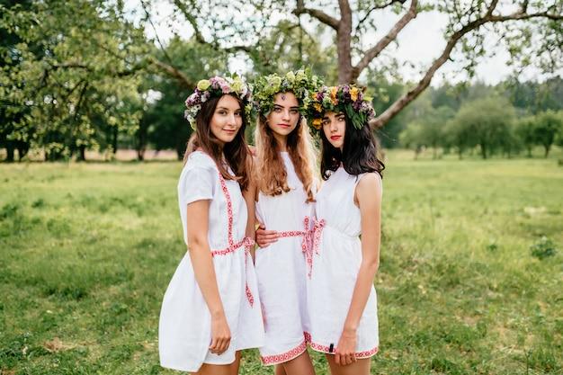 Três moças no retrato ao ar livre dos vestidos étnicos brancos.